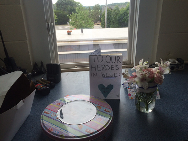"""ANDREA HOLBROOK/Staff photo<br /> The Essex Police Deprtment this weekend received a box of cookies, left, a tin of brownies, cards and a bouquet from """"some fans, a family from Ipswich, and one from Essex,"""" said Officer Rob Gilardi, adding that the treats were """"really good."""""""