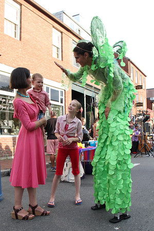 Leah Abel of Circus Up tries to get a high five from a young reveler Saturday during Gloucester's first block party of the season, held downtown. Vincenzo Dimino/Photo