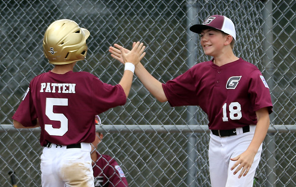 DAVID LE/Staff photo. Gloucester's Jack Patten is greeted by teammate Jack Viera after crossing the plate with a Gloucester run. 7/2/16.