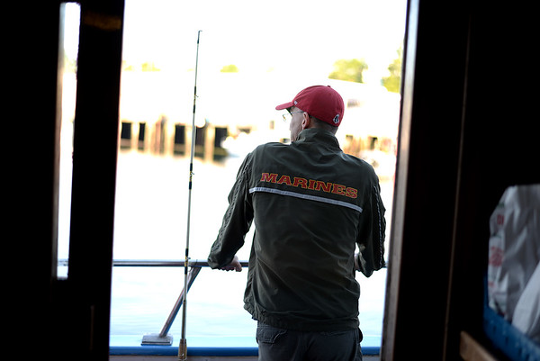 PAUL BILODEAU/Staff photo. Marine Veteran Filipe Carvalho take sin the sites of Gloucester Harbor before heading out to fish for the day. Dave Marciano of Wicked Tuna and Tom Orrell of the Yankee Fleet hosted a fishing trip to benefit the Wounded Warrior Project.