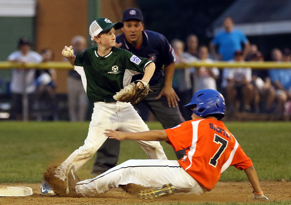 DAVID LE/Staff photo. Manchester-Essex shortstop Ryan Andrews steps around a sliding runner and looks to throw to first against Beverly in the District 15 Final on Thursday evening. 7/14/16.