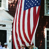 PAUL BILODEAU/Staff photo A large American Flag hangs from a home on Central Street during the annual Fourth of July Manchester-by-the-Sea parade