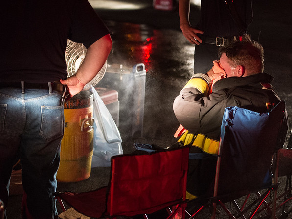 Desi Smith Photo.     Essex Firefighter Dave Thompson sits jn front of a fan showering him with light mist of water knocking down a fire insiade a business complex located at 239 Western Ave in Essex,Monday night on the fourth of July.