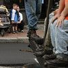 Gloucester: Tyler Giacalone, 4, of Gloucester watches the paving trucks drive up Main Street with his sister Victoria, 2, and mom Kristen Thursday.  Tyler liked watching the men working and would hold his hand out over the street to feel the heat off the hot tar. Mary Muckenhoupt/Gloucester Daily Times