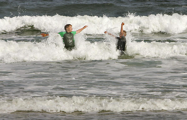 Gloucester: Alex Krabbendam, 12 and his brother Ethan, 10, play jump in the waves while enjoying the day at Good Harbor Beach Wednesday afternoon. The boys were having such a great time plying in the rough surf that they didn't seem to notice how chilly the water was. Mary Muckenhoupt/Gloucester Daily Times