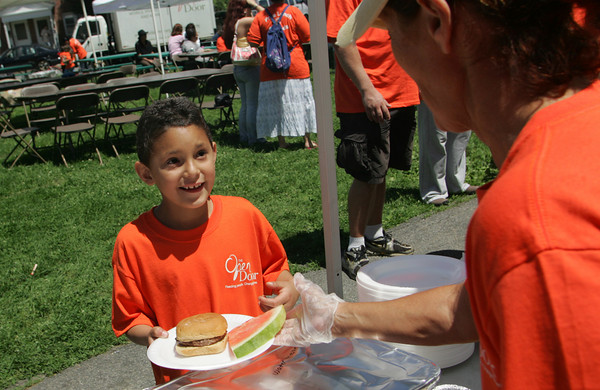 Gloucester:  Josten Maisonet, 8, takes a slice of watermelon at the Summer Lunch Kick-Off Picnic at Riverdale Park Thursday afternoon.  Summer Lunch is a 10-week program offering free lunch for kids age one to 18 in six locations on Cape Ann including Willowood Gardens, Cape Ann YMCA, Veterans Memorial School, Open Door Dining Room, Kitefield Road. Program is a partnership between The Open Door, Gloucester and Rockport Housing Authorities, Gloucester School Food Service and the Cape Ann YMCA.  Mary Muckenhoupt/Gloucester Daily Times