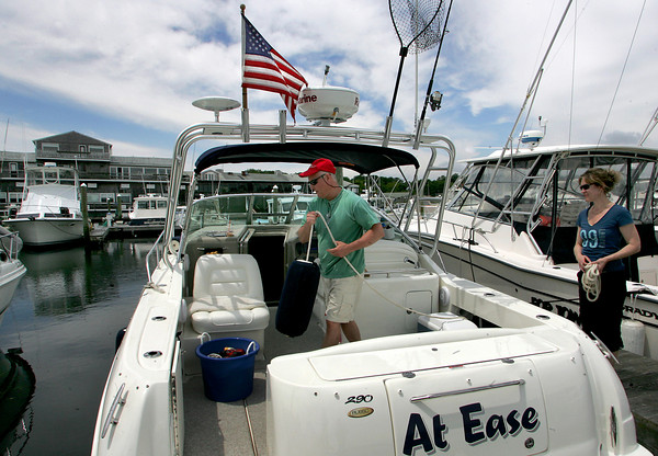 """Gloucester: Dave and Nancy Curtis dock their boat at Cape Ann Marina afetr a morning out on the water Saturday. The Curtis', who recently purchased this boat, say they haven't given up boating even though the economy is down. """"This is our vacation,"""" says Nancy."""