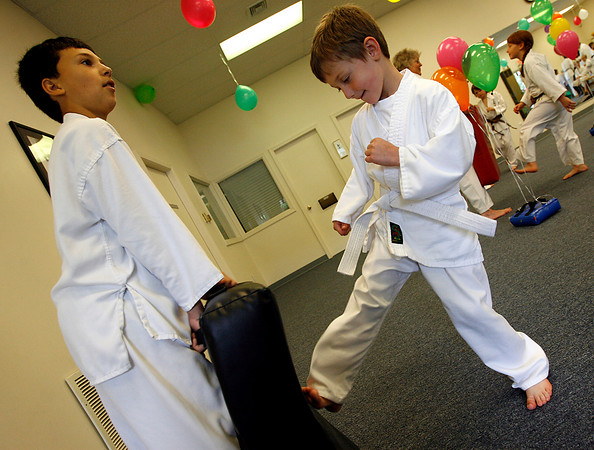 Gloucester: Jacob Diamanco, 10, holds the padding as Aiden Aiello, 5, kicks as long as he can during a kick-a-thon for St. Jude Children's Research Hospital at Mahaney's Uechi Karate Academy on Saturday. Photo by Kate Glass/Gloucester Daily Times Saturday, June 6, 2009