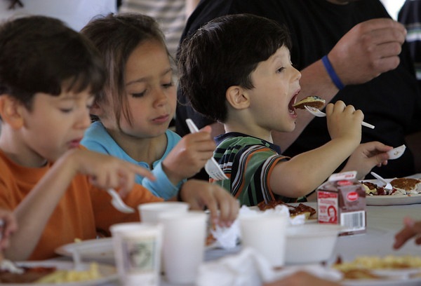 Manchester: Benjamin Vala, 5, takes a big bite of his pancake during the 19th annual Red, White and Blue Breakfast sponsored by the Manchester Essex Rotary Club at Tuck's Point Saturday morning.  The menu included eggs, bacon and pancakes topped with blueberries, strawberries and whipped cream. Also pictured is Isabella Eliassen, 6, and John Vala, 6, left. Mary Muckenhoupt/Gloucester Daily Times
