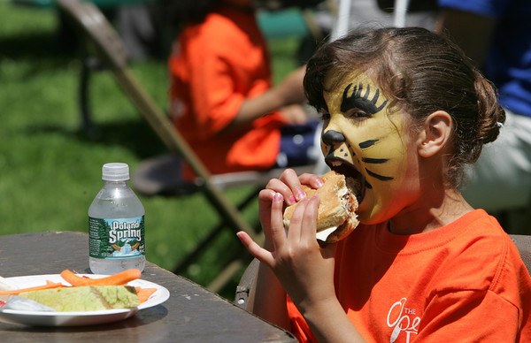 Gloucester:  Zorielys Maisonet, 7, takes a big bight of her hamburger at the Summer Lunch Kick-Off Picnic at Riverdale Park Thursday afternoon.  Summer Lunch is a 10-week program offering free lunch for kids age one to 18 in six locations on Cape Ann including Willowood Gardens, Cape Ann YMCA, Veterans Memorial School, Open Door Dining Room, Kitefield Road. Program is a partnership between The Open Door, Gloucester and Rockport Housing Authorities, Gloucester School Food Service and the Cape Ann YMCA.  Mary Muckenhoupt/Gloucester Daily Times