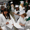 Manchester: Elsa Keefe, left, and Alli Pine sign yearbooks with the class of 2009 before graduation at Manchester Essex High School Friday evening. Mary Muckenhoupt/Gloucester Daily Times