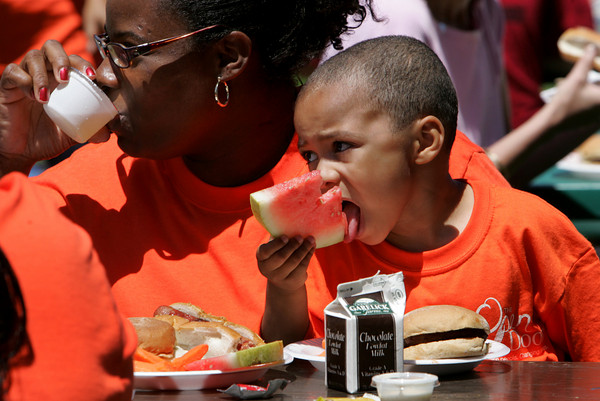 Gloucester:  Aidan DuBois, 3, eats a slice of watermelon while having lunch with his mom Dani at the Summer Lunch Kick-Off Picnic at Riverdale Park Thursday afternoon.  Summer Lunch is a 10-week program offering free lunch for kids age one to 18 in six locations on Cape Ann including Willowood Gardens, Cape Ann YMCA, Veterans Memorial School, Open Door Dining Room, Kitefield Road. Program is a partnership between The Open Door, Gloucester and Rockport Housing Authorities, Gloucester School Food Service and the Cape Ann YMCA.  Mary Muckenhoupt/Gloucester Daily Times