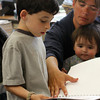 "Gloucester: Benjamin Haight shows his mother, Laura, and brother Bryant, 9 months, the book he made titled ""Video Games"" in MaryAnn Goodhue's first grade class during Family Day at West Parish Elementary School Friday.  Each child in the first grade classes made a book that they showed to their parents over a breakfast in their classrooms. Mary Muckenhoupt/Gloucester Daily Times"