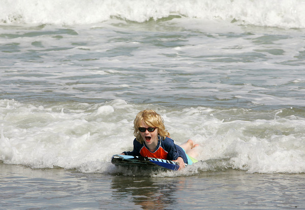 Gloucester: Gus Johnson, 6, of Rockport rides a wave in to greet his mom who was watching from the water's edge while playing at Good Harbor Beach Wednesday afternoon.  Mary Muckenhoupt/Gloucester Daily Times