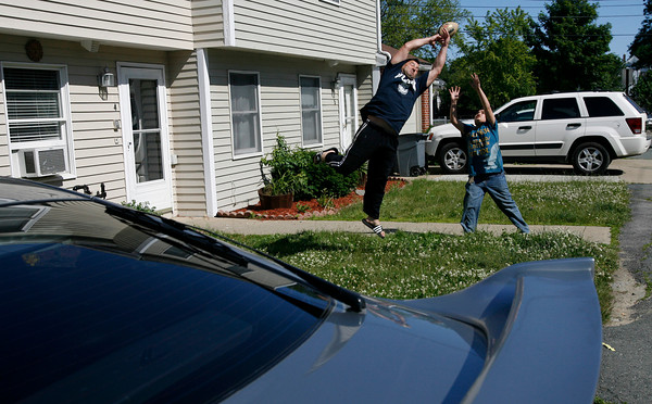 Gloucester: Giovanni Oliva, left, and Accursio Oliva, 12, play catch over cars on Sargent Street with Emilio Oliva (not shown) yesterday afternoon. Photo by Kate Glass/Gloucester Daily Times Tuesday, June 16, 2009