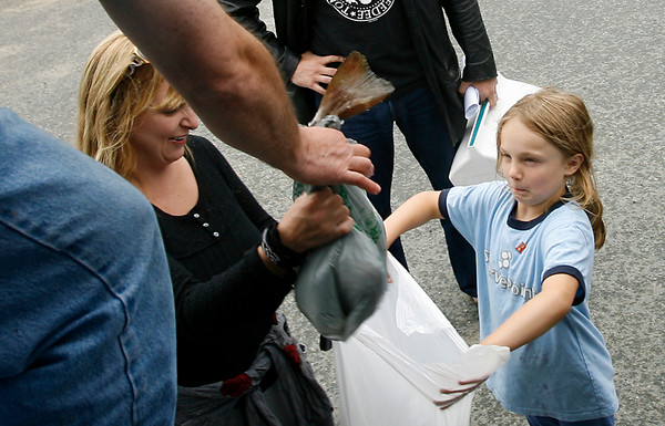 """Gloucester: Willow Phoenix, 7, center, makes a face as Steve Parkes hands her and her mother, Shawna Phoenix, cod from Cape Ann Fresh Fish, a Community Supported Fishery. """"You don't know what you're going to get so it forces you to be creative,"""" Shawna Phoenix says. Photo by Kate Glass/Gloucester Daily Times Thursday, June 18, 2009"""