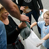 "Gloucester: Willow Phoenix, 7, center, makes a face as Steve Parkes hands her and her mother, Shawna Phoenix, cod from Cape Ann Fresh Fish, a Community Supported Fishery. ""You don't know what you're going to get so it forces you to be creative,"" Shawna Phoenix says. Photo by Kate Glass/Gloucester Daily Times Thursday, June 18, 2009"