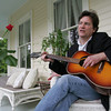 "Gloucester: Thomas Hauck sings a song on the porch of his Gloucester Home Friday afternoon.  Hauck wrote ""Pistonhead"", a novel about a man who works on an assembly line and plays guitar in a rock band. Mary Muckenhoupt/Gloucester Daily Times"