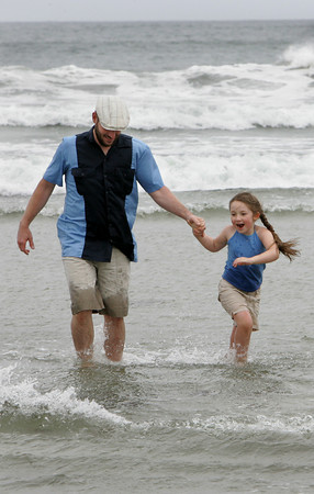 Gloucester:  Maeve McInnis, 5, walks out of the water with her dad Daren at Good Harbor Beach Tuesday afternoon. Maeve was having a blast running around in the water so she took her dad in for a walk in the chilly water. Maeve then tried to get her grandfather to go in the water but had no luck. Mary Muckenhoupt/Gloucester Daily Times