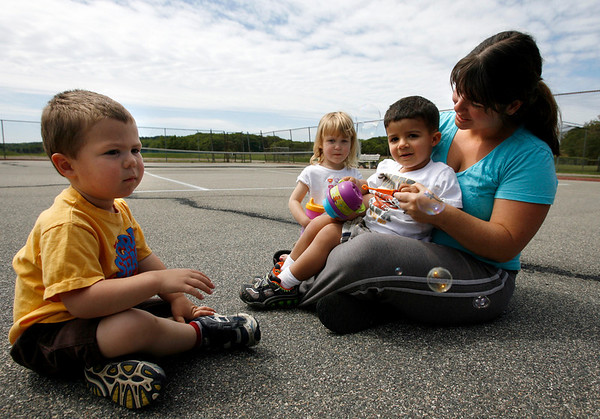 Essex: Rian Docarmo blows bubbles with William Lowthers, left, Abby Lowthers, center, and Logan Docarmo, right, at the tennis courts in Essex on Wednesday morning. Photo by Kate Glass/Gloucester Daily Times Wednesday, June 3, 2009