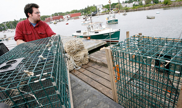 Manchester: David Heath of Manchester loads lobster traps onto his father's boat, Intuition, yesterday morning as they prepare to put them back into the water. Photo by Kate Glass/Gloucester Daily Times Tuesday, June 2, 2009