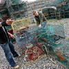 Rockport: Justus Dunton, left, tosses a piece of rope into the trash as he and Andrew Deschenes, right, help Scott Place (not shown) retag his lobster traps at Granite Pier on Tuesday afternoon. Photo by Kate Glass/Gloucester Daily Times Tuesday, June 30, 2009