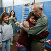 Gloucester: Brittany Burke hugs West Parish Elementary Principal Jim Gutstadt as her classmate, Aisha Frontiero, looks on during the last day of school yesterday. Gutstadt, who has been at the school 16 years, is retiring. Photo by Kate Glass/Gloucester Daily Times Monday, June 22, 2009