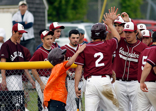 Gloucester: Members of the Gloucester baseball team congratulate Ross Carlson after he scored their first run against Lawrence in the second round of the North Division I tournament yesterday. Photo by Kate Glass/Gloucester Daily Times Monday, June 1, 2009
