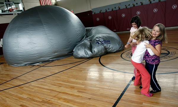 Rockport: Sophie Moulton, right, smiles as she gets a hug from Katie White, left, and Sarah Palmer after watching the Museum of Science's Night Sky program at Rockport Elementary School yesterday. The event was the first part of the Rockport Library's Summer Reading program, but was held at the school because of the size of the planetarium. Photo by Kate Glass/Gloucester Daily Times Wednesday, June 24, 2009