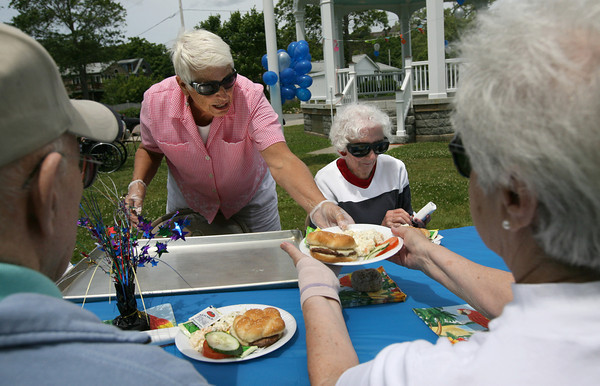 Rockport: Kathy Tettoni hands out plates of hamburgers and salad during the Neighbors Caring for Neighbors summer barbecue on the Legion grounds yesterday afternoon. The barbecue was hosted by Den Mar Rehabilitation and Nursing Center and the Rockport Council on Aging. To Tettoni's right is Kay Daigle. Photo by Kate Glass/Gloucester Daily Times