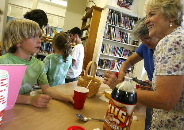 Essex: Jonah Tomaiolo gets a root beer float from Bonnie Bradford and Beth Cairns, right, at the T.O.H.P. Burnham Library on Monday afternoon as the library kicks off its summer reading program. Photo by Kate Glass/Gloucester Daily Times