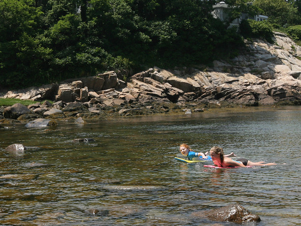Gloucester: Kelsea and Morgan Arsenault float around Folly Cove Thursday afternoon. The two were trying to avoid touching barnacles on the rocks. Photo by Kate Glass/Gloucester Daily Times