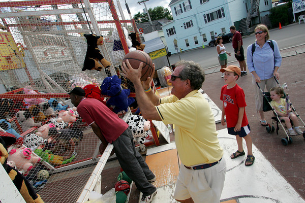 Gloucester: Steve Warhover of Gloucester aims for the basket while playing Hoop Shot, one of the games at the carnival for Fiesta Wednesday evening.  Also pictured is Warhover's grandson Jackson Warhover, daughter Susan Buckheit and granddaughter Jane Buckheit. Mary Muckenhoupt/Gloucester Daily Times