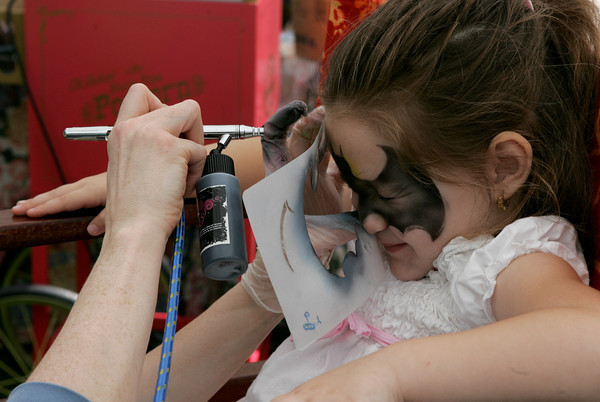 Gloucester: Jessica Cote, 4, of Gloucester squints as she has a bat painted on her face by Kristine Karvelas at Celebration of the Sea, a Cape Ann Family Festival at the Eastern Point Day School Saturday.  The event included shopping with local artisans, tale-telling pirates, giant puppets and more. Mary Muckenhoupt/Gloucester Daily Times