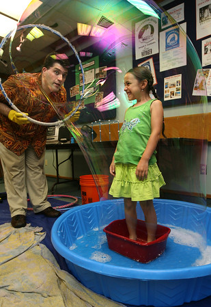 "Gloucester: Ava Vitale giggles as Mike Dorval, the ""Boston Bubble Guy"" puts her in a bubble during the Sawyer Free Library's summer reading program kick off on Tuesday morning. Photo by Kate Glass/Gloucester Daily Times"