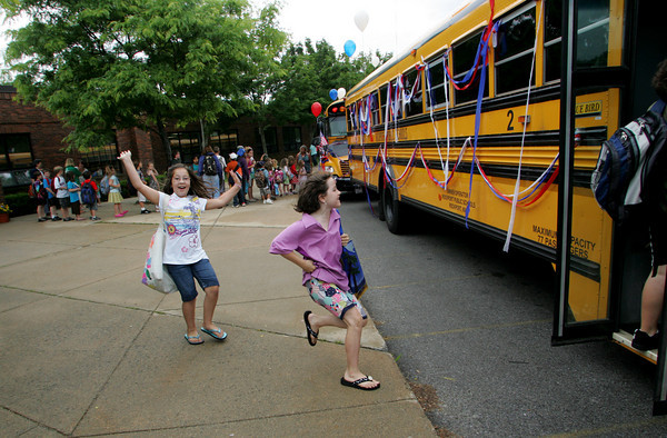 Rockport: Olivia Lattof, left, and Anna Young run to their bus decorated for the last day of school in front of Rockprot Elementary School Thursday afternoon. Mary Muckenhoupt/Gloucester Daily Times