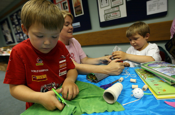 Gloucester: George King, left, cuts fabric for his fish puppet while his mom, Catherine, helps his brother, Charles, make a train puppet following Rosalita's Puppets at the Sawyer Free Library on Wednesday morning. Photo by Kate Glass/Gloucester Daily Times