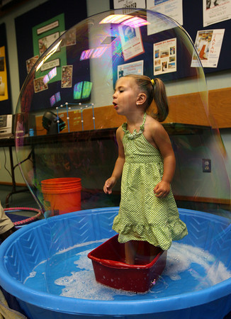 Gloucester: Ava Coelho, 2, gets put in a bubble during a program to start the Sawyer Free Library's summer reading program on Tuesday morning. Photo by Kate Glass/Gloucester Daily Times