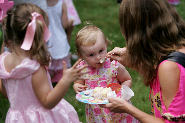 Manchester: Lucy Romans, 14 months, takes a bite of pink frosted cake from her mother, Jen, while attending the Pinkalicious Tea Party at the Manchester Library with her sister Olivia, 3, left, Wednesday afternoon. Mary Muckenhoupt/Gloucester Daily Times