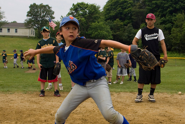 Gloucester: Kyle Kariores throws the ball to first base while running a double play drill with the Gloucester High School baseball team including Joey Avila, right, during the 5th Annual Gloucester Little League Family Picnic & Skills Day at Boudreau Field Saturday. The day included a variety of fun activieties including a dunk tank, home run derby, hit the target and much more. Mary Muckenhoupt/Gloucester Daily Times