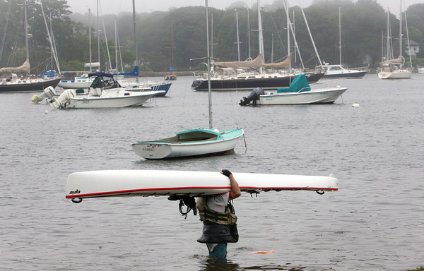 Manchester: Leon Granowitz turns his kayak upside down before heading out of the water at Tuck's Point Wednesday afternoon. Granowitz and his wife had paddled to Danvers and back, almost 20 miles, to prepare for the upcoming Blackburn Challenge, a kayak race around Cape Ann. Mary Muckenhoupt/Gloucester Daily Times
