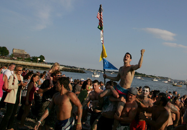 Gloucester: Friday night greasy pole winner Joe Brancaleone gets carried onto Pavilion beach. Mary Muckenhoupt/Gloucester Daily Times