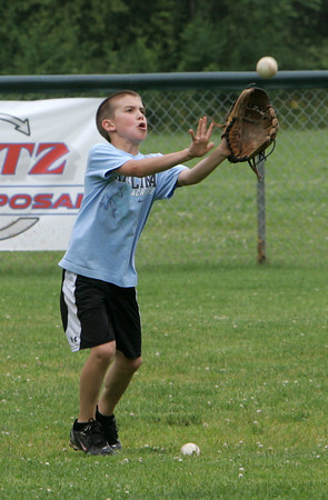 Manchester: Jake Athanas, 9, catches a ball hit to him by his dad while working on catching fly balls at Sweeney Park Wednesday afternoon. Mary Muckenhoupt/Gloucester Daily Times