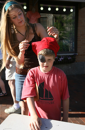 Gloucester: Amelia Leonards of Cape Ann Art Haven helps Yishai Howe, 6, tie a bandana he decorated to dress like a pirate during the block party on Saturday night. Photo by Kate Glass/Gloucester Daily Times<br /> , Gloucester: Amelia Leonards of Cape Ann Art Haven helps Yishai Howe, 6, tie a bandana he decorated to dress like a pirate during the block party on Saturday night. Photo by Kate Glass/Gloucester Daily Times
