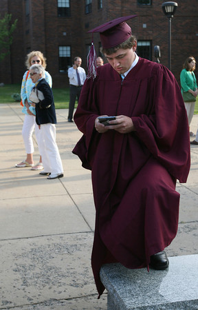 Rockport: Mike Foote sends out a text as he gets ready for the graduation ceremony at Rockport High School last night. Photo by Kate Glass/Gloucester Daily Times