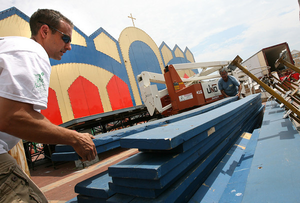 Gloucester: Joe Novello and his son, John Novello, move the bleachers at St. Peter's Square to get a lift through so they can take down the electrical wiring of the altar yesterday afternoon. Photo by Kate Glass/Gloucester Daily Times