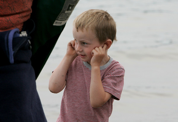 Gloucester: Jeramy Adamson, 4, of Rockport holds his ears as firecrackers are set off from a boat in the harbor while watching the greasy pole with his family on Pavilion beach Saturday. Mary Muckenhoupt/Gloucester Daily Times
