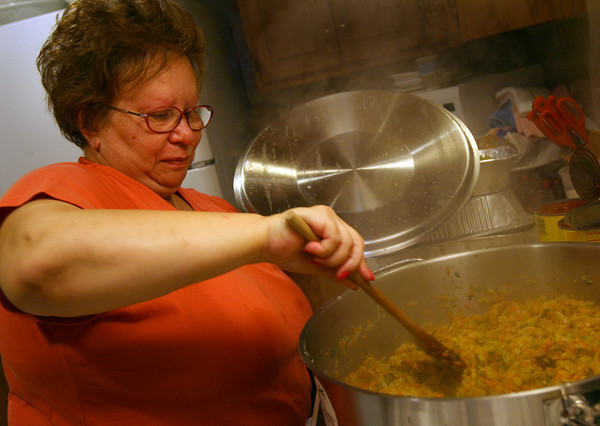 Gloucester: Angela Sanfilippo of the Fishermen's Wives Association mixes onions, celery, carrots and parsley together as the base for their monkfish stew, which is one of three dishes the association prepared for the New Fish Festival at the Gloucester House last night. Photo by Kate Glass/Gloucester Daily Times