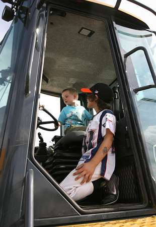 "Manchester: Lucas Waugh, 9, keeps an eye on his cousin, Andrew Rosenthal, 3, as they climb on construction equipment behind Manchester Town Hall during the ""Touch A Truck"" event on Tuesday night. Photo by Kate Glass/Gloucester Daily Times"