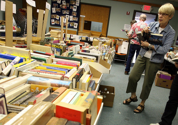 """Gloucester: Rosella Sagall organizes books into categories at the Sawyer Free Library yesterday afternoon. The """"Friends of the Library Annual Book & Bake Sale is open for """"friends only"""" tonight from 4-7 and tomorrow from 9-1 for the public. Photo by Kate Glass/Gloucester Daily Times"""